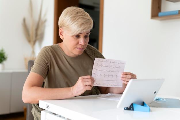 Mulher doente com tiro médio segurando eletrocardiograma