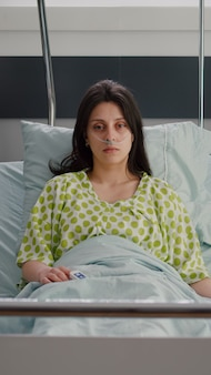 Mulher doente com tubo de oxigênio nasal olhando para a câmera, descansando na cama se recuperando após cirurgia respiratória