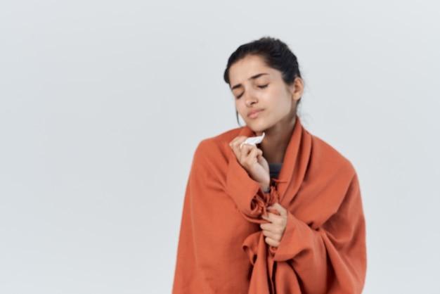 Mulher doente com um cobertor nos ombros uma infecção pelo resfriado