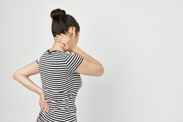 Mulher doente com uma camiseta listrada, dor no pescoço, problemas de saúde