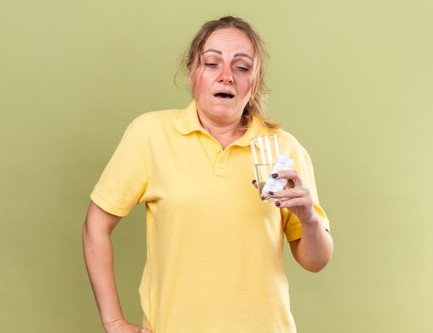 Mulher doente de camisa amarela se sentindo péssima segurando um copo d'água e comprimidos contra a gripe indo espirrar em pé sobre a parede verde