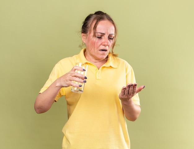 Mulher doente de camisa amarela se sentindo péssima segurando um copo d'água e comprimidos indo tomar remédios contra gripe e resfriado em pé sobre uma parede verde