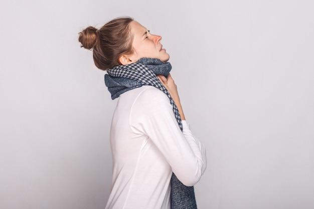 Mulher doente de vista de perfil tocando seu pescoço, tem tosse, dor de garganta. foto de estúdio