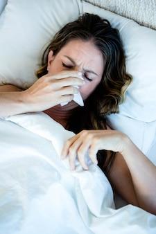 Mulher doente, deitada em sua cama, assoando o nariz em um lenço de papel