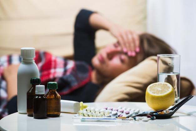 Mulher doente deitado no sofá sob o cobertor de lã