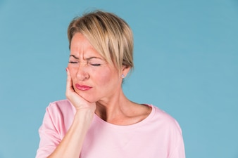 Mulher doente descontente tendo dor de dente e tocar sua bochecha