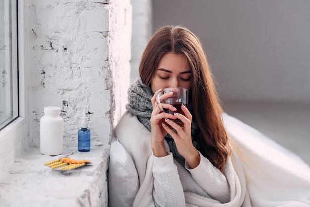 Mulher doente doente beber bebida de aquecimento dentro de casa