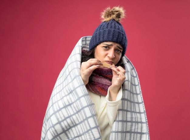 Mulher doente e carrancuda usando um manto de inverno, chapéu e cachecol embrulhado em xadrez segurando um gesso médico na frente do queixo, olhando para a frente, isolado na parede rosa