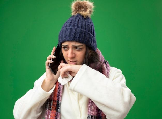 Mulher doente e carrancuda usando um manto de inverno, chapéu e cachecol, falando no telefone, segurando o guardanapo, mantendo a mão perto da boca, olhando para o lado isolado na parede verde