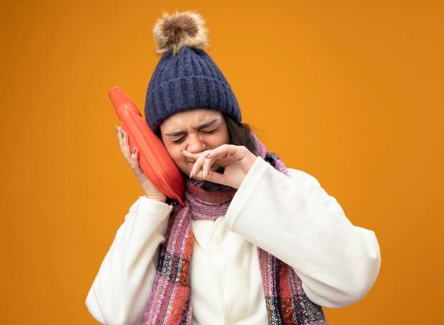 Mulher doente e carrancuda usando um manto de inverno, chapéu e lenço tocando a cabeça com um saco de água quente, limpando o nariz com os olhos fechados, isolado na parede laranja