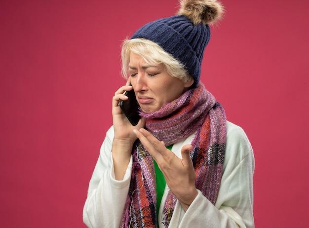 Mulher doente e doente, chateada, com cabelo curto, usando um lenço quente e um chapéu, sentindo-se mal, chorando enquanto fala no celular, em pé sobre uma parede rosa
