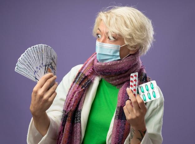 Mulher doente e doente com cabelo curto em um lenço quente e máscara protetora facial segurando dinheiro e pílula parecendo confusa e preocupada com dúvidas em pé sobre a parede roxa