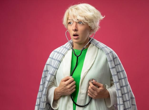 Mulher doente e doente com cabelo curto enrolado em um cobertor com estetoscópio no pescoço ouvindo os batimentos cardíacos, sentindo-se mal e preocupada em pé sobre um fundo rosa