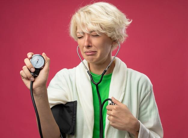Mulher doente e doente e chateada com cabelo curto com estetoscópio medindo sua pressão arterial, chorando e sentindo mal-estar em pé sobre uma parede rosa