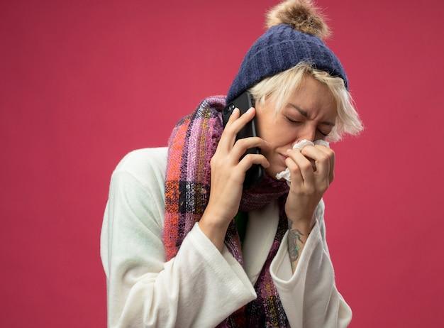 Mulher doente e doente e chateada com cabelo curto em um lenço quente e chapéu, sentindo mal-estar chorando enquanto fala no celular, limpando o nariz com um guardanapo em pé sobre um fundo rosa