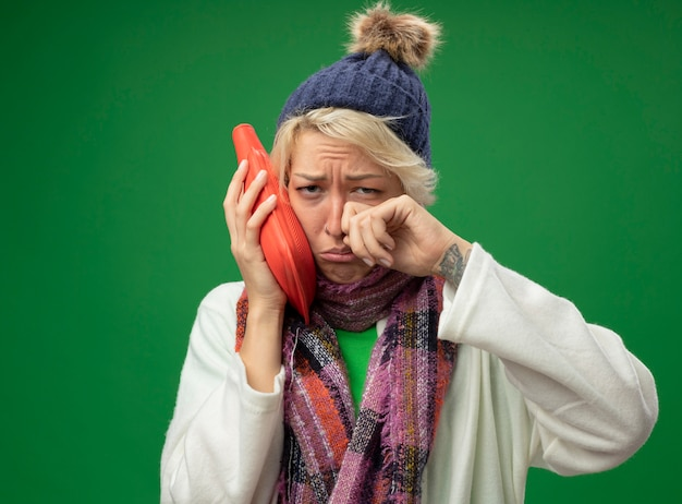 Mulher doente e doente e chateada com cabelo curto em um lenço quente e um chapéu, sentindo-se indisposta segurando uma garrafa de água para manter o choro quente em pé sobre uma parede verde