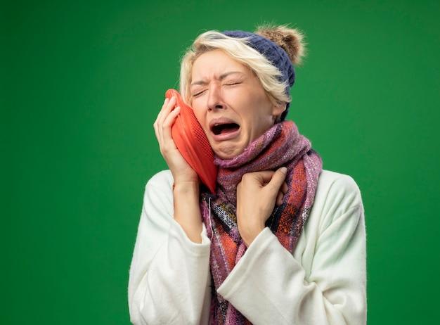Mulher doente e doente e chateada com cabelo curto em um lenço quente e um chapéu, sentindo-se mal, segurando uma garrafa de água para manter o choro quente em pé sobre fundo verde
