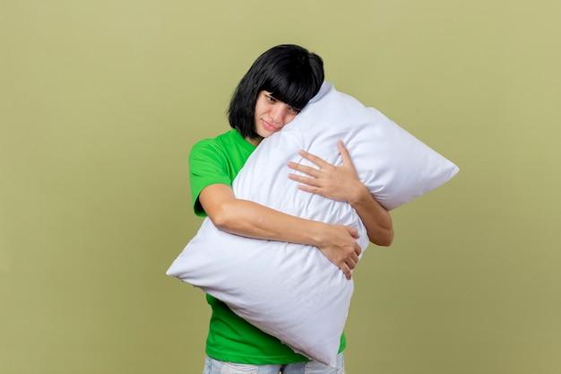 Mulher doente e fraca abraçando o travesseiro, olhando para baixo, isolada na parede verde oliva