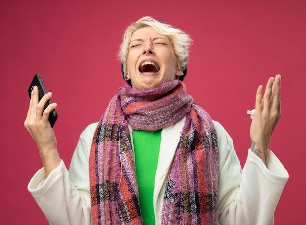 Mulher doente e insalubre chateada com cabelo curto em um lenço quente e um chapéu se sentindo mal