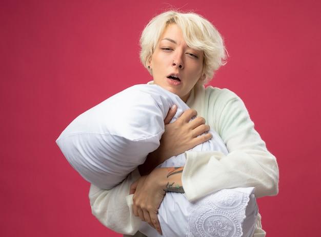 Mulher doente e insalubre com cabelo curto abraçando o travesseiro, sentindo-se indisposta muito doente, sofrendo de gripe e espirrando em pé sobre um fundo rosa