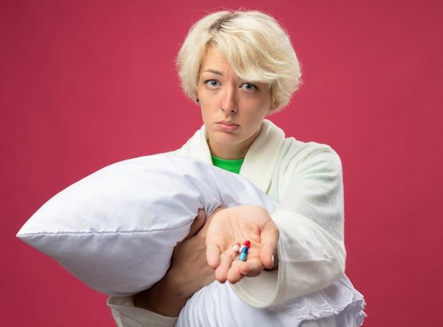Mulher doente e insalubre com cabelo curto abraçando o travesseiro, sentindo-se mal, mostrando comprimidos no braço com uma expressão triste em pé sobre um fundo rosa