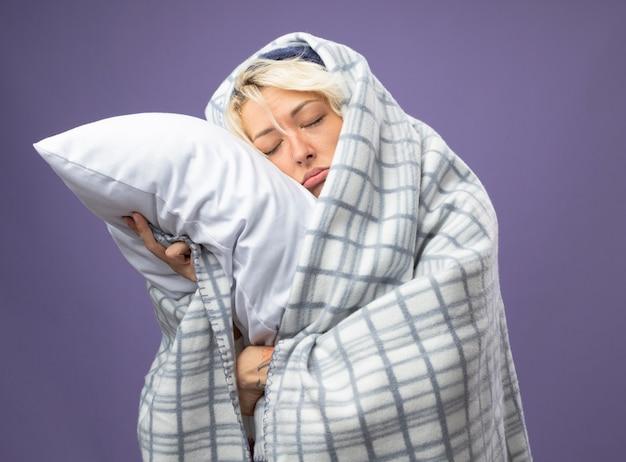 Mulher doente e insalubre com cabelo curto em um chapéu quente enrolado em um cobertor, segurando o travesseiro, apoiando a cabeça no travesseiro com os olhos fechados, infeliz com o fundo roxo