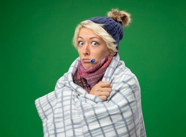 Mulher doente e insalubre com cabelo curto em um lenço quente e chapéu se sentindo mal enrolada em um cobertor com termômetro na boca em pé sobre um fundo verde