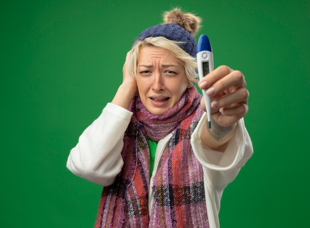 Mulher doente e insalubre com cabelo curto em um lenço quente e chapéu se sentindo mal, mostrando o termômetro sendo infeliz e preocupada em pé sobre um fundo verde