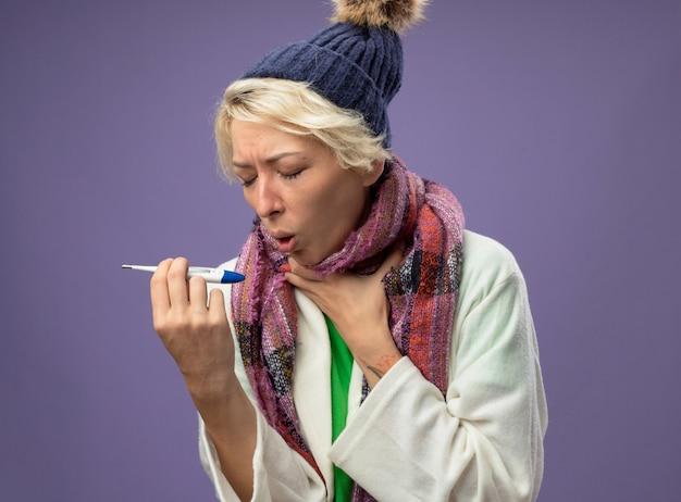 Mulher doente e insalubre com cabelo curto em um lenço quente e chapéu se sentindo mal segurando um termômetro, tossindo, sofrendo de gripe, em pé sobre um fundo roxo