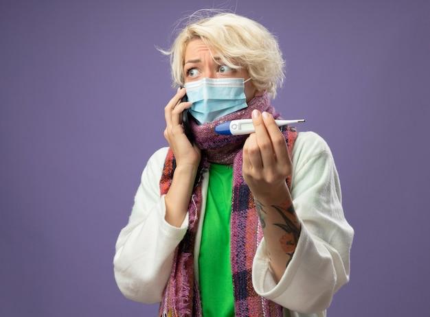Mulher doente e insalubre com cabelo curto em um lenço quente e máscara protetora facial segurando um termômetro, parecendo preocupada enquanto fala ao telefone móvel, apoiada na parede roxa