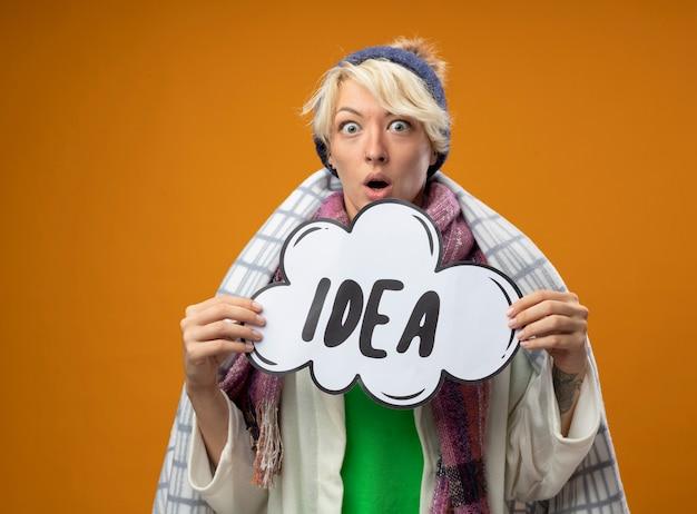 Mulher doente e insalubre com cabelo curto em um lenço quente e um chapéu embrulhado em um cobertor segurando um cartaz de bolha do discurso com a palavra ideia, olhando para a câmera espantada e surpresa de pé sobre um fundo laranja