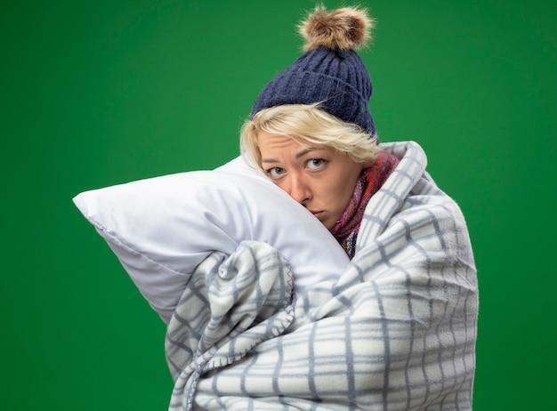 Mulher doente e insalubre com cabelo curto em um lenço quente e um chapéu se sentindo mal, enrolada em um cobertor, abraçando um travesseiro, olhando para a câmera com tristeza sobre fundo roxo