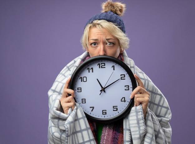 Mulher doente e insalubre com cabelo curto em um lenço quente e um chapéu se sentindo mal, enrolada em um cobertor, segurando um relógio de parede, olhando para a câmera preocupada com o fundo roxo