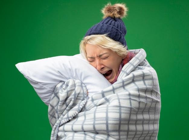 Mulher doente e insalubre com cabelo curto em um lenço quente e um chapéu se sentindo mal, enrolada em um cobertor, segurando uma almofada, chorando em pé sobre um fundo verde
