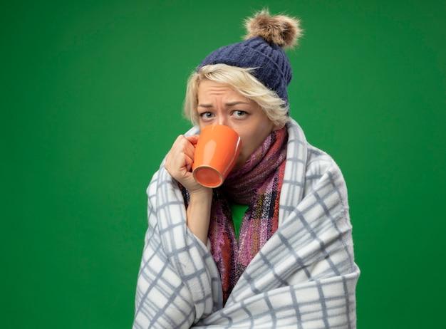 Mulher doente e insalubre com cabelo curto em um lenço quente e um chapéu se sentindo mal enrolada em um cobertor, sofrendo de febre, bebendo chá quente em pé sobre um fundo verde