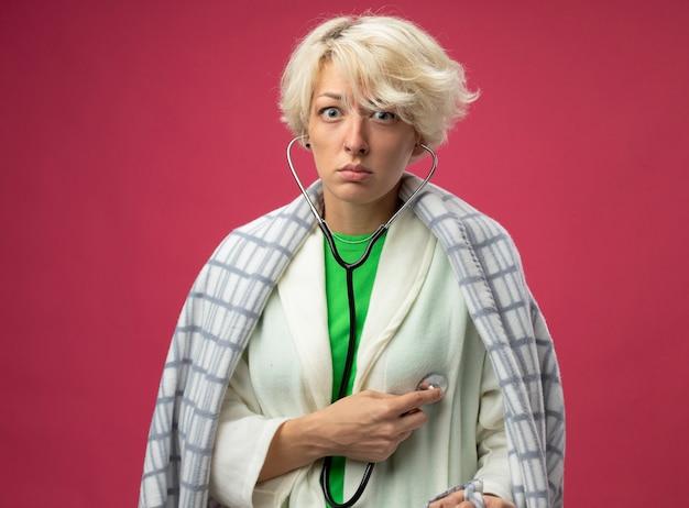 Mulher doente e insalubre com cabelo curto enrolado em um cobertor com estetoscópio no pescoço ouvindo seus batimentos cardíacos, sentindo mal-estar em pé sobre um fundo rosa