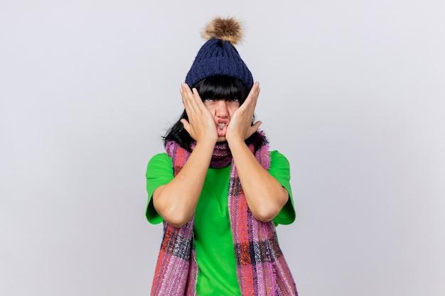 Mulher doente e irritada com chapéu e lenço de inverno, olhando para cima, mantendo as mãos no rosto isoladas na parede branca