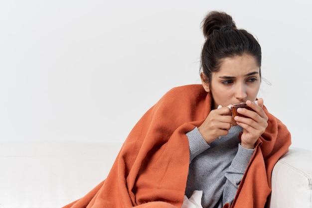 Mulher doente em casa coberta com um cobertor bebendo chá. foto de alta qualidade