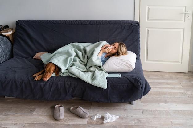Mulher doente em casa deitada na cama com seu cachorro vizsla, sofrendo de alergia, sintoma de gripe, febre