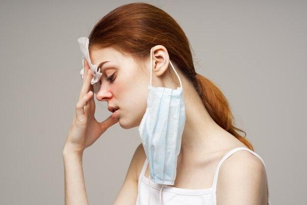 Mulher doente em uma camiseta branca com um lenço de fundo claro