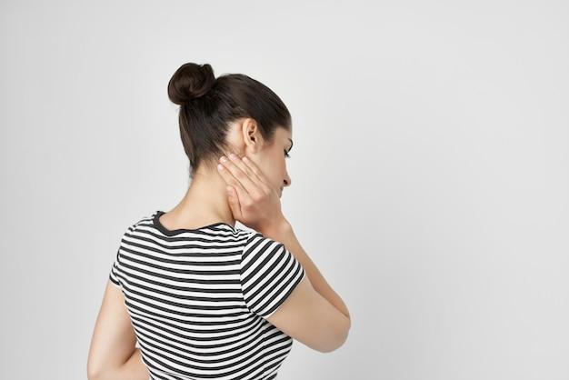 Mulher doente em uma t-shirt listrada dor nos problemas de saúde do pescoço. foto de alta qualidade