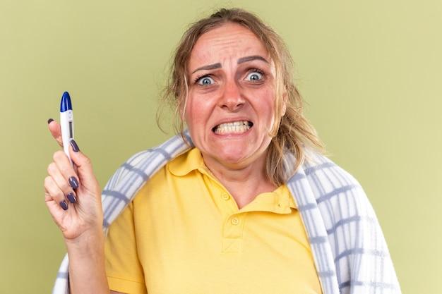 Mulher doente enrolada em um cobertor se sentindo mal, sofrendo de gripe e resfriado, tendo febre segurando um termômetro, louca e frustrada