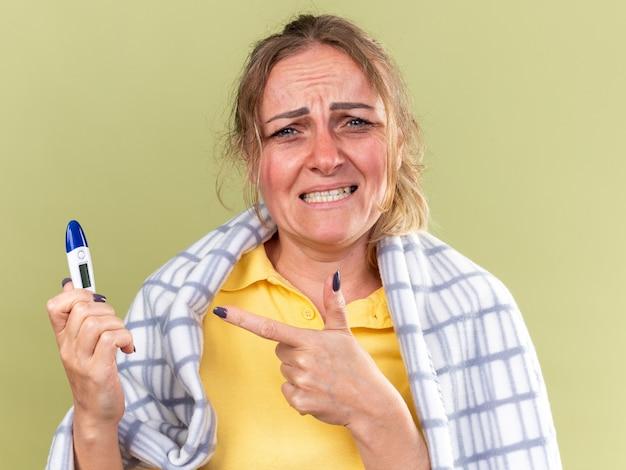 Mulher doente enrolada em um cobertor sentindo terrível, sofrendo de gripe e resfriado segurando um termômetro apontando com o dedo indicador para ele parecendo assustada