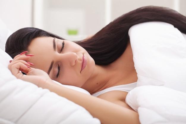 Mulher doente. gripe. menina com frio deitado debaixo de um cobertor segurando um lenço de papel