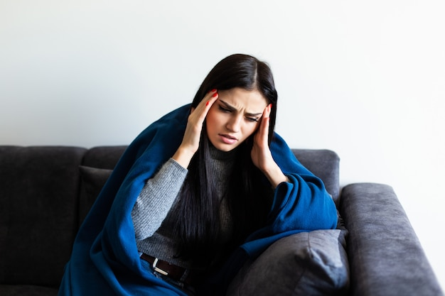 Mulher doente indisposta, sentindo sua temperatura enquanto descansava no sofá em casa