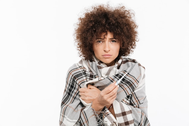 Mulher doente infeliz em pé envolto em um cobertor