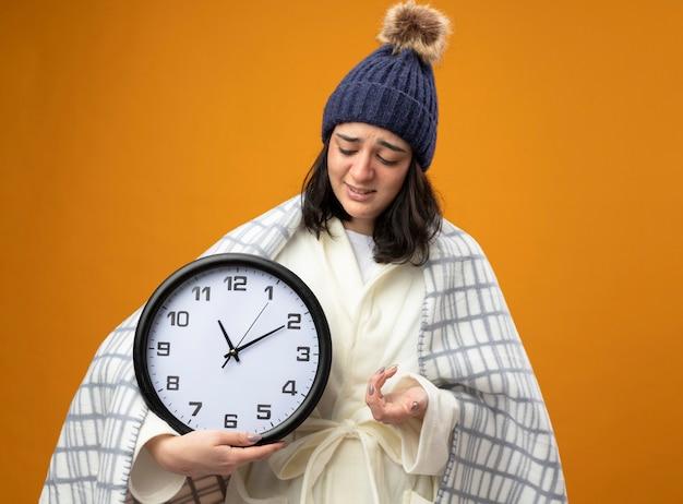 Mulher doente jovem irritada usando um manto de inverno, um chapéu envolto em uma manta, apontando com a mão e olhando para o relógio isolado na parede laranja