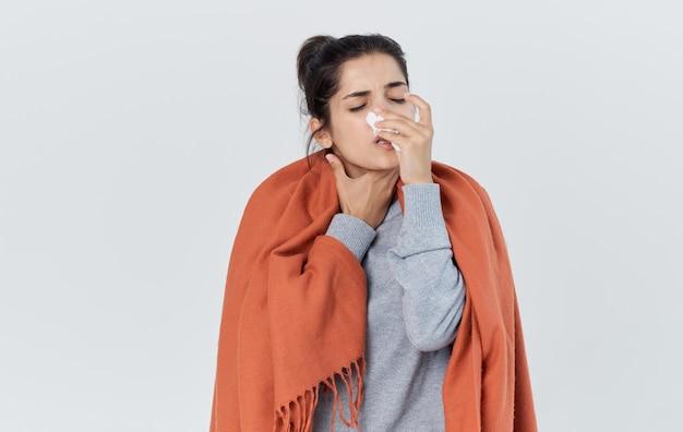 Mulher doente limpa o nariz com uma infecção de gripe em um lenço