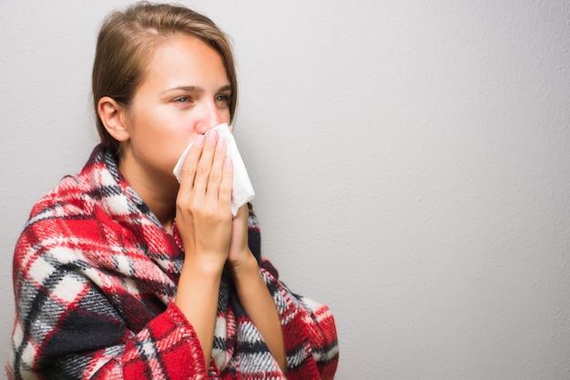 Mulher doente, limpando o nariz