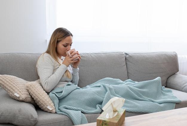 Mulher doente na cama com febre alta, bebendo chá